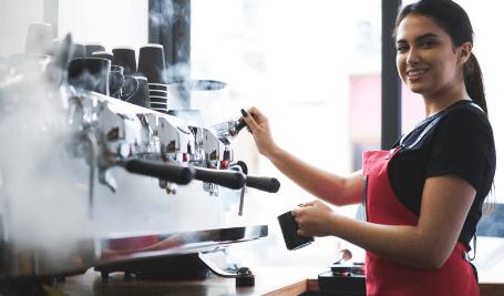 Imagem de uma mulher fazendo café em uma máquina de café expresso